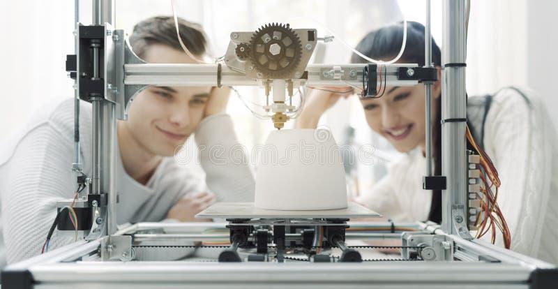 Teknikstudenter som använder en skrivare 3D i labbet arkivfoto