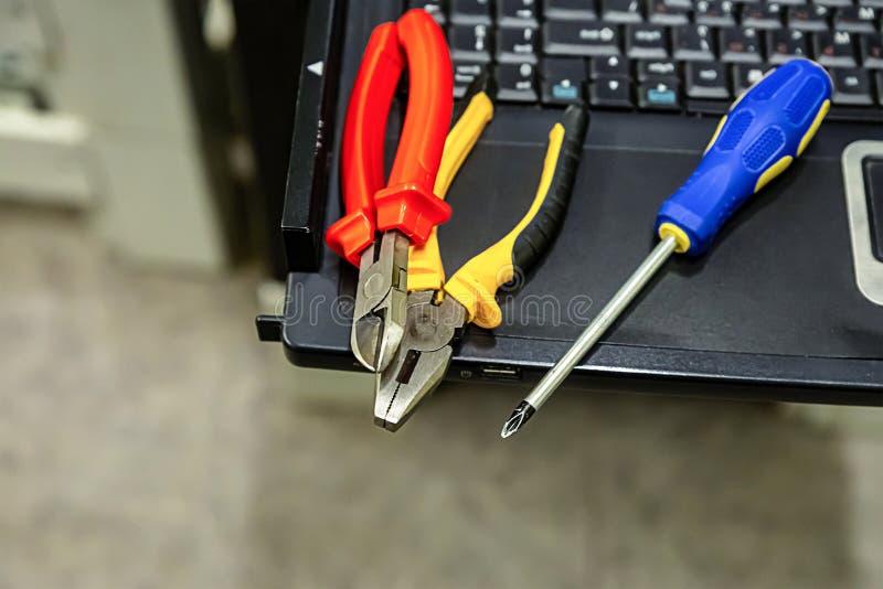 Teknisk skruvmejsel för reparation för förbättring för dator för hjälpmedeluppsättning som klipper plattång på tangentbordbakgrun royaltyfri foto