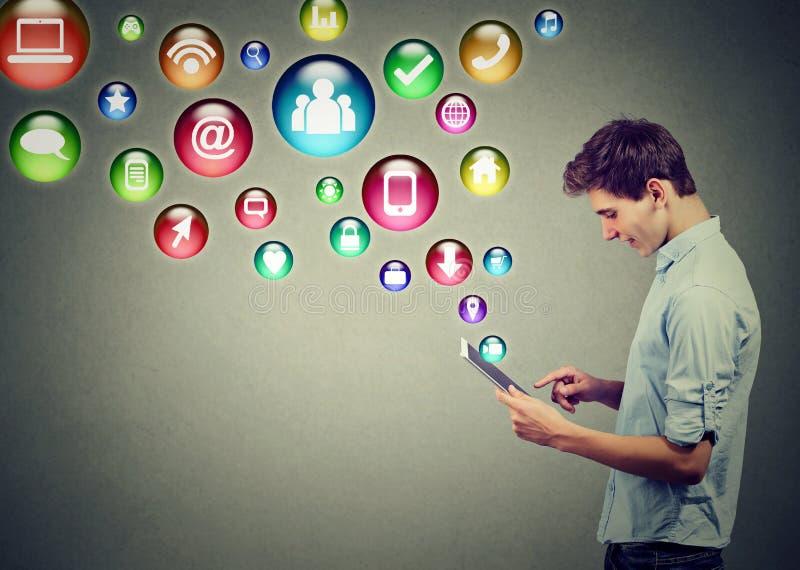 Tekniskt avancerat begrepp för mobil teknologi Sidoprofil av en man som använder minnestavladatoren med sociala massmediaapplikat royaltyfri foto