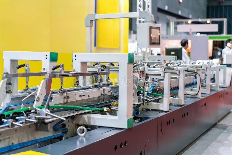 Tekniskt avancerat och automatiskt modernt av maskinen för den pappersasken eller lådan som gör i industriellt royaltyfri fotografi