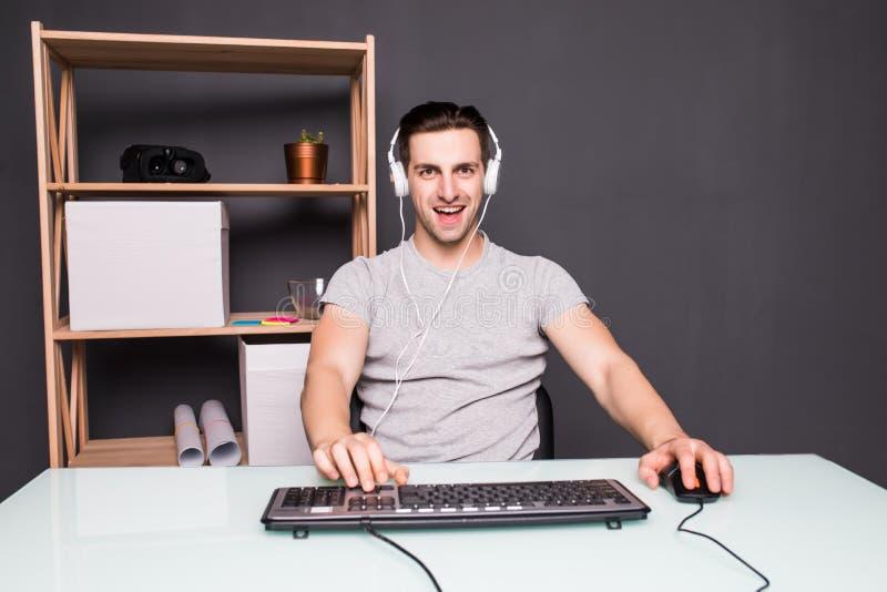 Teknologi dobbel, underhållning, lät lek för ` s och folkbegreppet - skrikig ung man i hörlurar med mikrofon med PCdatoren som sp royaltyfri foto