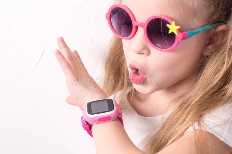 Teknologi för barn: en flicka som bär rosa exponeringsglas, använder en smartwatch fotografering för bildbyråer