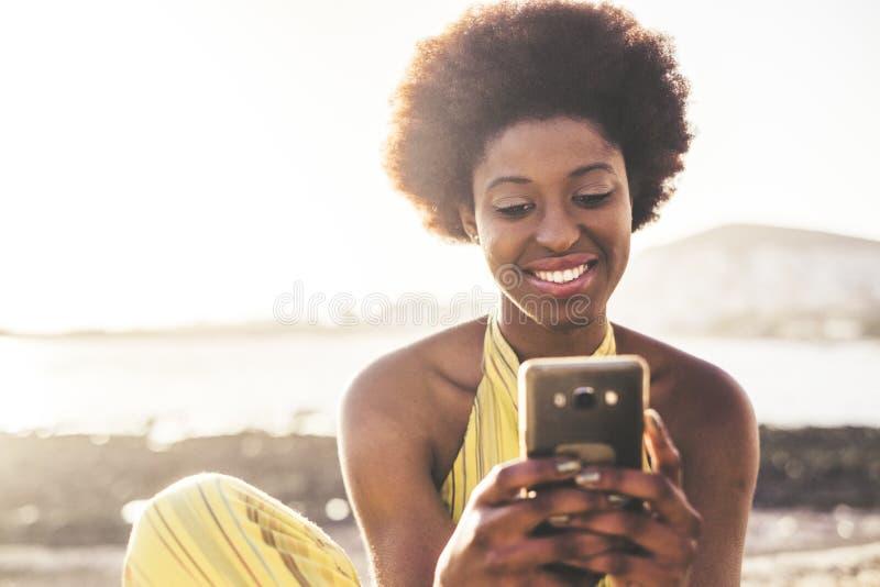 Teknologi för mobiltelefon för bruk för hår för härlig ung rac för modellflickasvart afrikansk som skriver vänner under en semest arkivbild