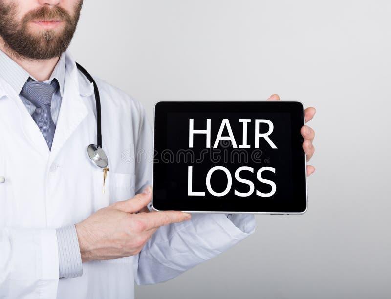 Teknologi, internet och nätverkande i medicinbegrepp - manipulera att rymma en minnestavlaPC med tecknet för hårförlust Internet arkivbild