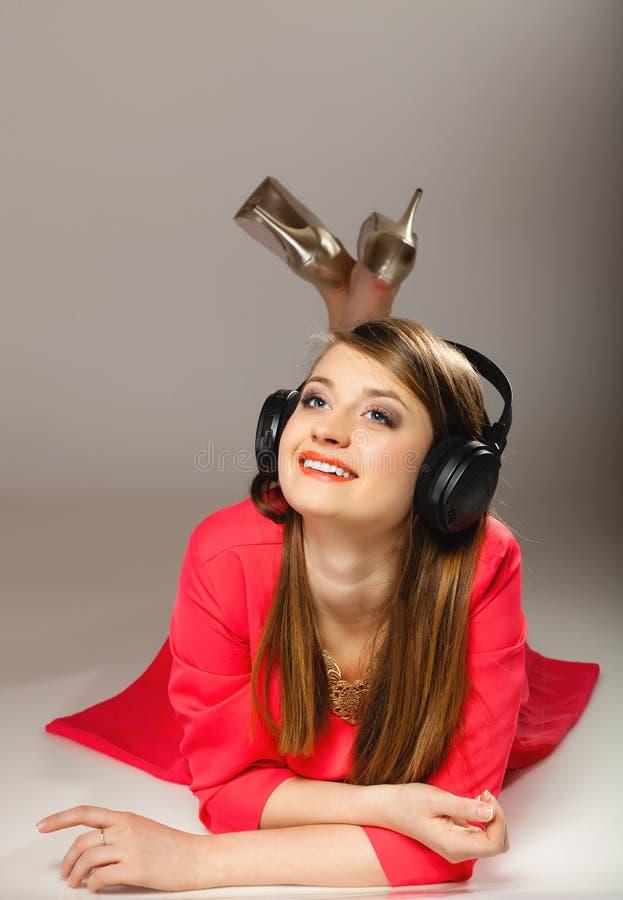 Teknologi musik - le den tonåriga flickan i hörlurar royaltyfria bilder