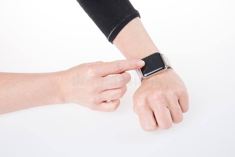 Teknologi och folkbegrepp med slut upp av kvinnahänder som ställer in den smarta klockan royaltyfri foto