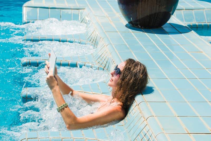 Teknologi- och semesterbegrepp Lyxigt lopp Ung nätt kvinna som använder minnestavladatoren, medan koppla av i brunnsortbubbelpool arkivfoto