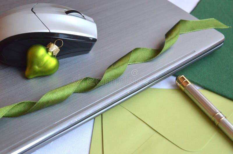 Teknologi på arbete under jul Den stängda bärbar datordatoren med musen, pennan, anmärkningskort och grön jul klumpa ihop sig gar arkivbild