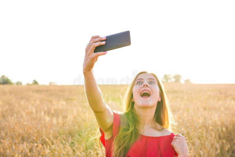 Teknologi, sommarferier, semester och folkbegrepp - le den unga kvinnan i den röda klänningen som tar selfie vid smartphonen royaltyfri fotografi
