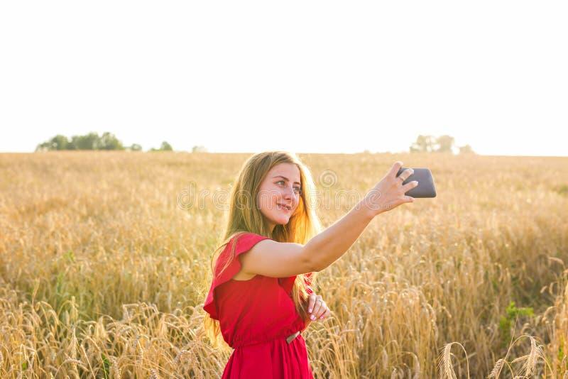 Teknologi, sommarferier, semester och folkbegrepp - le den unga kvinnan i den röda klänningen som tar selfie vid smartphonen royaltyfri bild