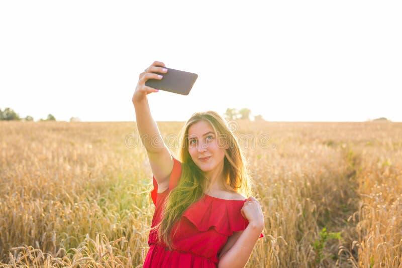 Teknologi, sommarferier, semester och folkbegrepp - le den unga kvinnan i den röda klänningen som tar selfie vid smartphonen arkivfoton