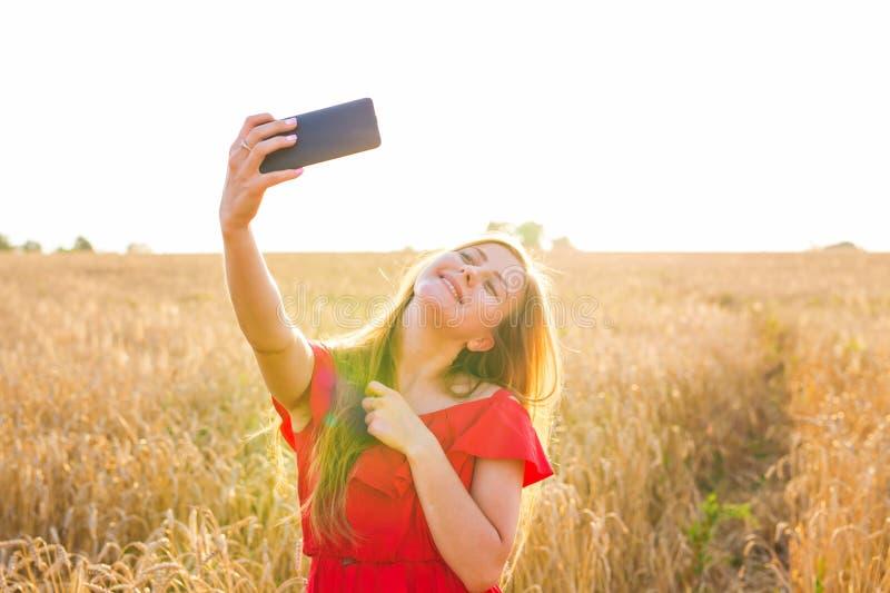 Teknologi, sommarferier, semester och folkbegrepp - le den unga kvinnan som tar selfie vid smartphonen på sädesslag royaltyfri bild