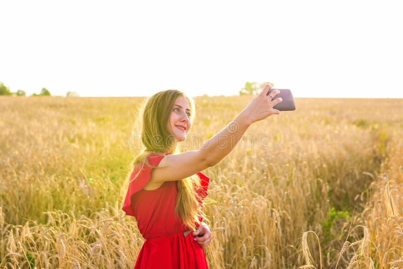 Teknologi, sommarferier, semester och folkbegrepp - le den unga kvinnan som tar selfie vid smartphonen på sädesslag royaltyfria foton