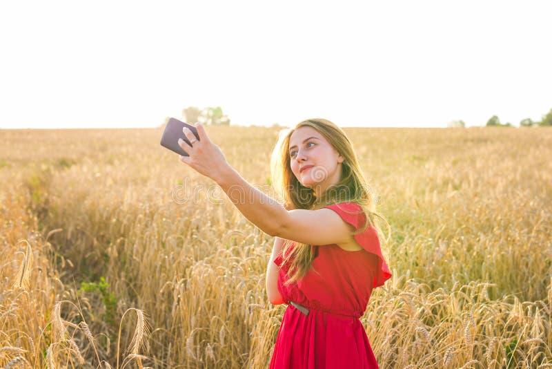 Teknologi, sommarferier, semester och folkbegrepp - le den unga kvinnan som tar selfie vid smartphonen på sädesslag royaltyfria bilder