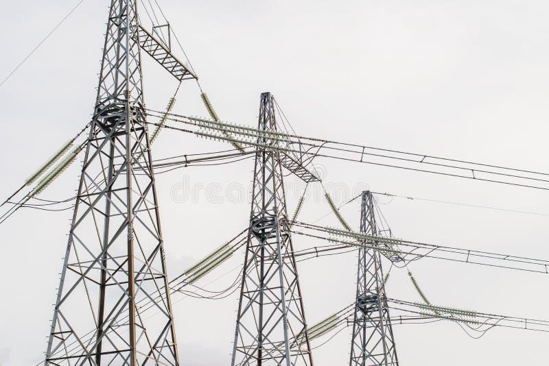 Teknologielektricitet på trådar med isolatorer och elektrisk spänning för hög makt arkivbild