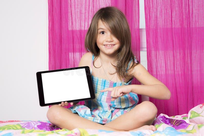 Teknologier blir lättare Gullig liten flicka som rymmer den digitala minnestavlan royaltyfri foto