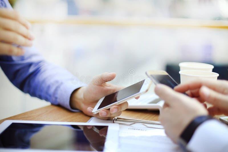 Teknologier gör liv lättare Närbild av mannen som rymmer den digitala minnestavlan medan mobiltelefon och bärbar dator arkivfoto