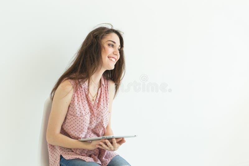 Teknologier sinnesrörelser, folkbegrepp - ung lycklig kvinna med minnestavlan i henne händer som ler över vit bakgrund med royaltyfria foton