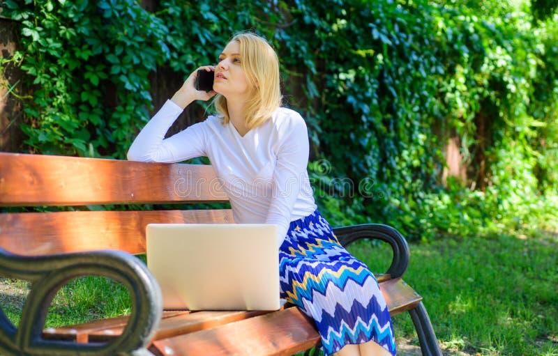 Teknologier som gör liv lättare Kvinnan med bärbara datorn arbetar utomhus Affärsdam som löser avlägsna problem flicka royaltyfria bilder
