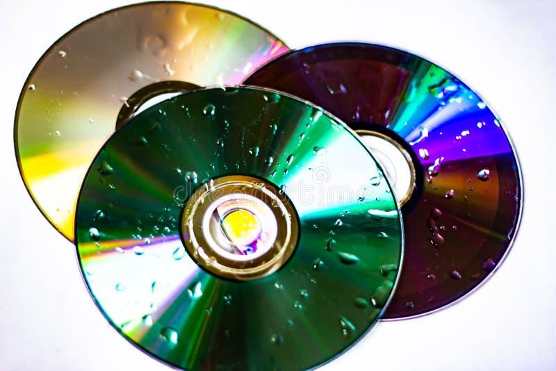 Teknologisk bakgrund skapade med fotoet av tre våta CD, ljuset accentuerar reflexionerna som färgar dem arkivbild