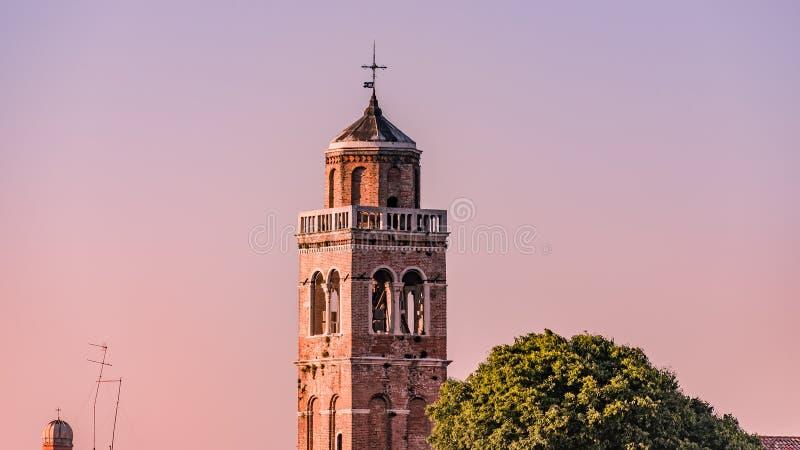 Teknologisk kontrast över åldrigt klockatorn med kors- och telekommunikationantenner, Venedig, Italien, sommartid royaltyfria foton
