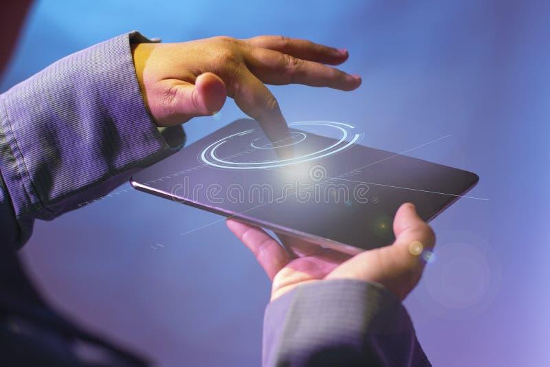 Teknologiska begrepp inför framtiden av digitala minnestavlor Tryck på minnestavlaskärmen och utfärda en våg av ljus som omringar fotografering för bildbyråer