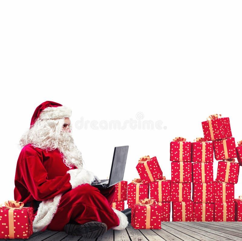 Teknologiska Santa Claus som sitter med bärbara datorn, köper julgåvor med e-kommers fotografering för bildbyråer