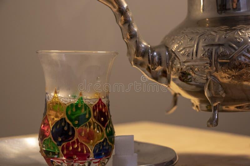 Tekokkärl med den marockanska designen som häller ett exponeringsglas av mintkaramellte royaltyfria bilder