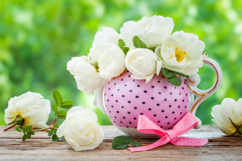 Tekokkärl och bukett av rosor arkivfoton