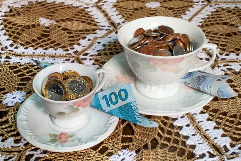 Tekoppar med brasilianska verkliga pengar inom royaltyfri foto