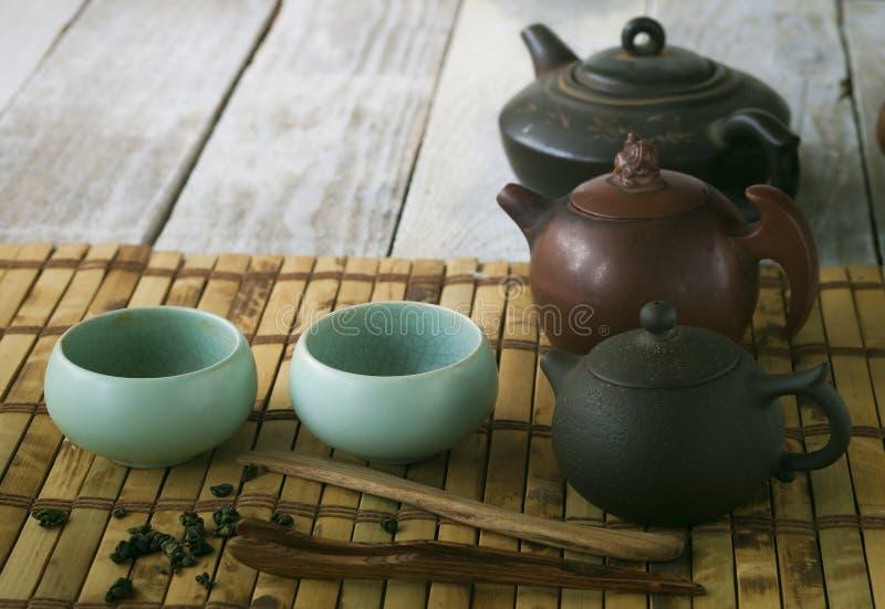 Tekruka och koppar på trätabellen arkivbild