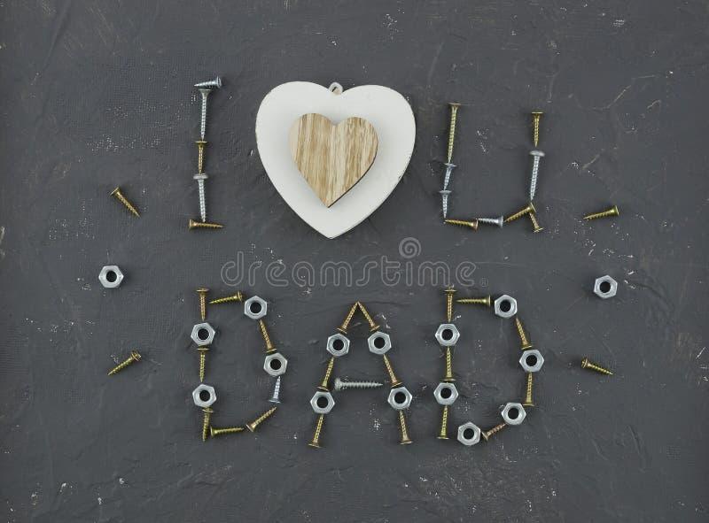 Tekst «kocham ciebie tata «dla ojca dnia z serca i literowania składem robić od śrub, śruby, dokrętka, gwoździe, śruby obrazy stock