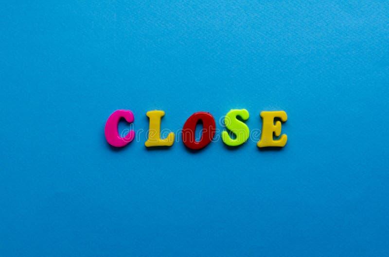 Tekst dicht van plastiek gekleurde brieven op blauwe document achtergrond stock foto