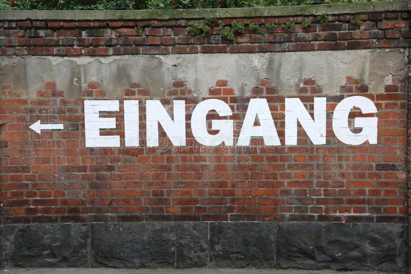 Tekst EINGANG op de bakstenen muur wat UITGANG in het Duits betekent stock foto