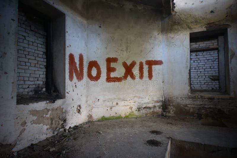 Tekst geen uitgang op de vuile oude muur in een verlaten geruïneerd huis stock afbeeldingen