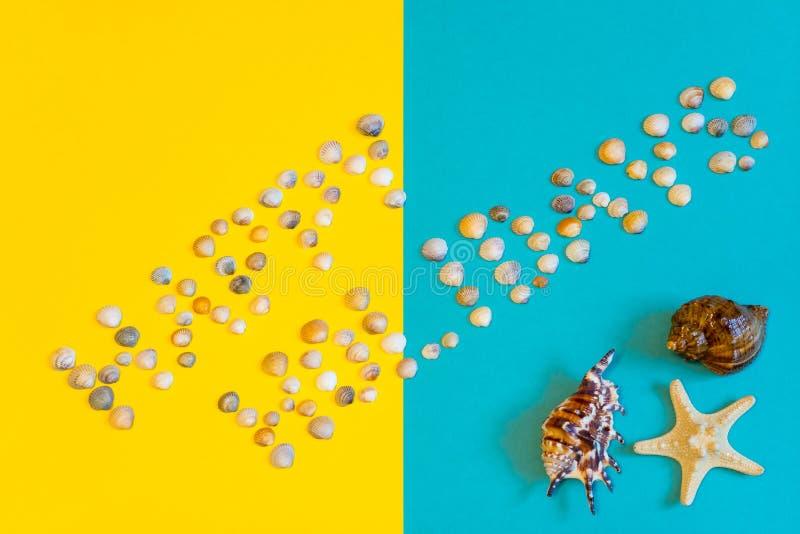 Tekst Gelukkige die Vakantie van kleine zeeschelpen op gele en blauwe document achtergrond met overzeese ster en overzeese shell  stock afbeeldingen