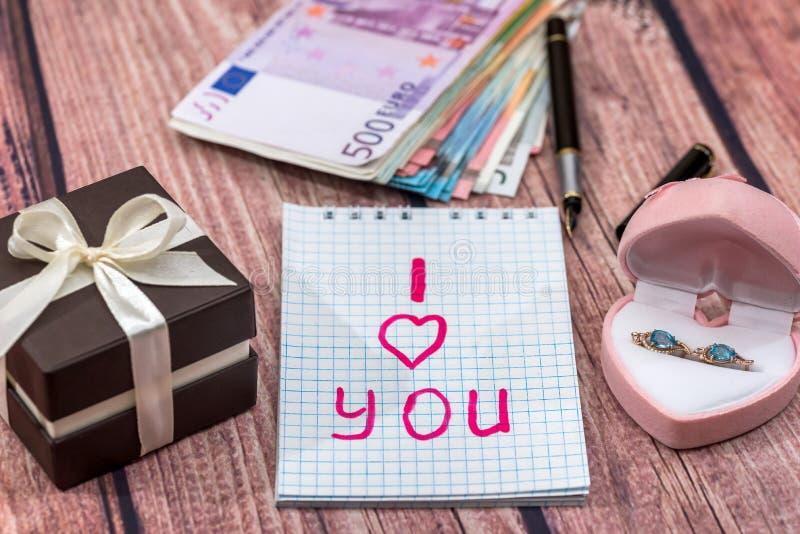 Tekst i houdt van u met gouden oorringen, geld stock foto