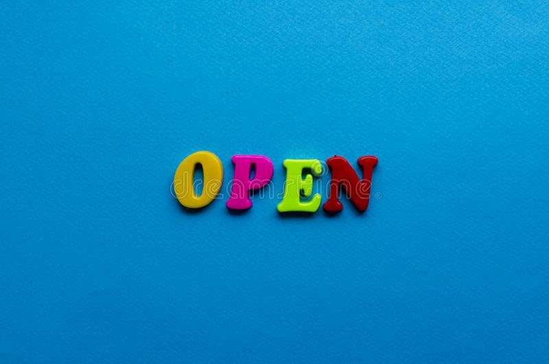 Tekst open van plastiek gekleurde brieven op blauwe document achtergrond stock foto