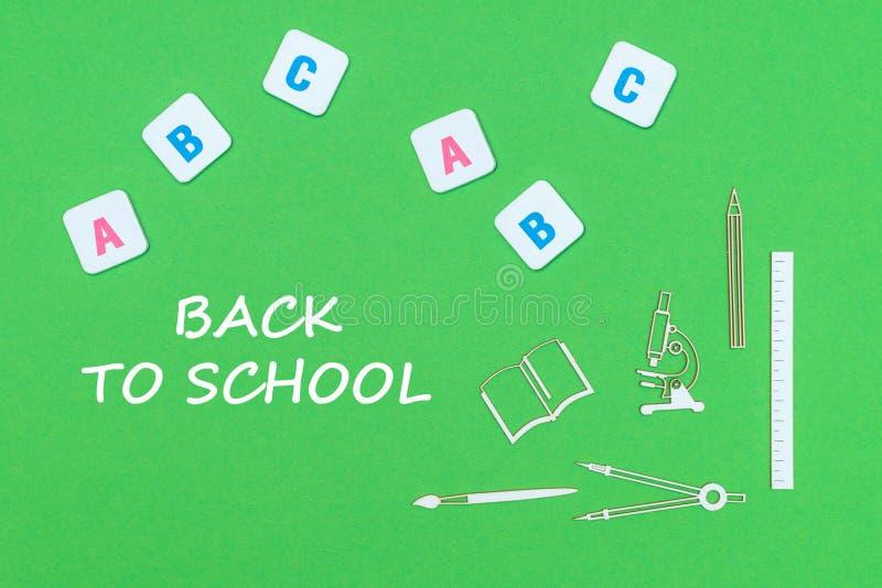 Tekst terug naar school, van boven de de houten levering en abc brieven van de minituresschool op groene achtergrond stock afbeeldingen