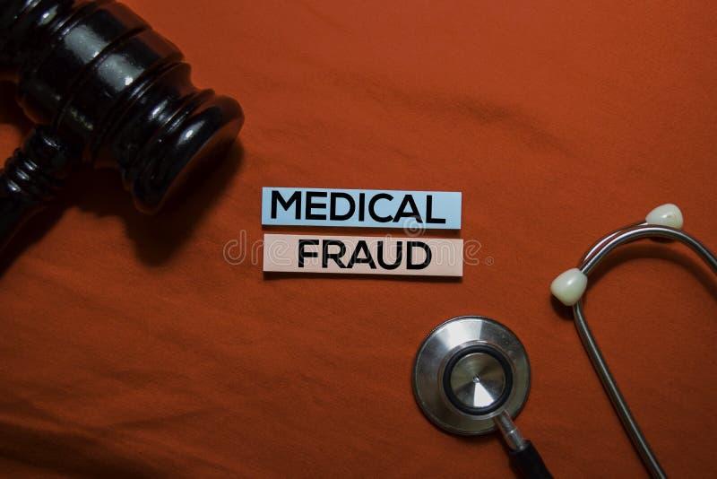 Tekst voor medische fraude op plakbiljetten met stethoscoop en een afmeting op kantoor stock foto