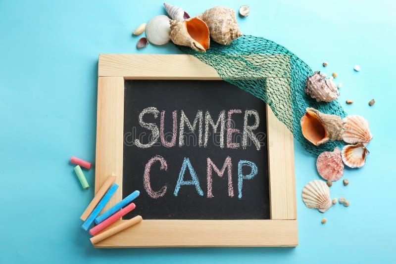 Teksta obóz letni na blackboard, kolorowej kredzie i skorupach, odgórny widok zdjęcie royalty free