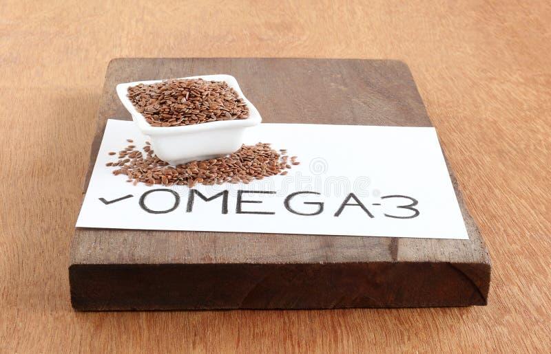 Teksta ` Omega-3 ` Ręcznie pisany na papieru i lna ziarnie obraz stock