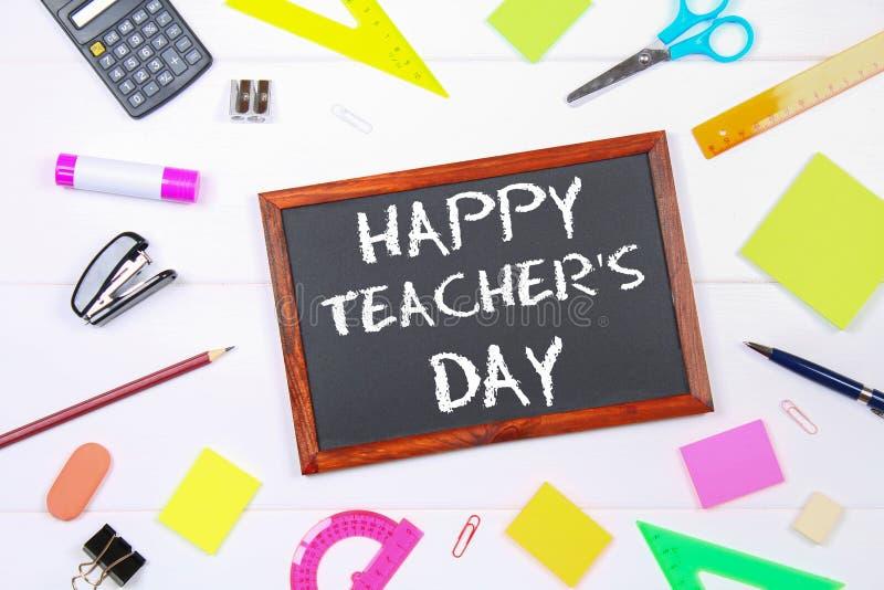 Tekstkrijt op een bord: Gelukkige Leraars` s Dag Schoollevering, bureau, boeken, appel stock foto's