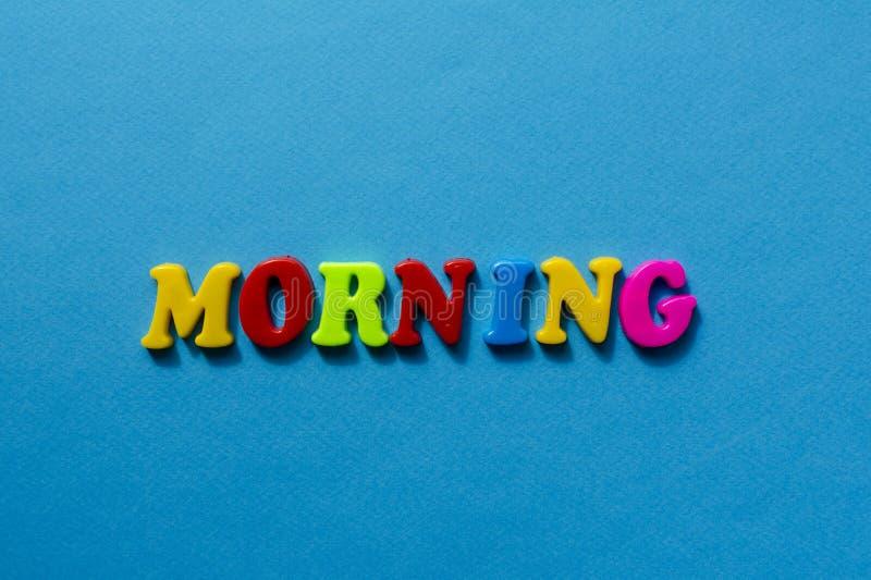 Tekstochtend van plastiek gekleurde brieven op blauwe document achtergrond royalty-vrije stock afbeelding