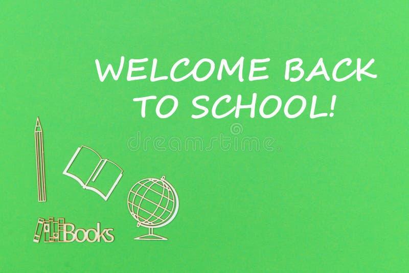 Tekstonthaal terug naar school, de houten miniaturen van de schoollevering op groene achtergrond stock fotografie