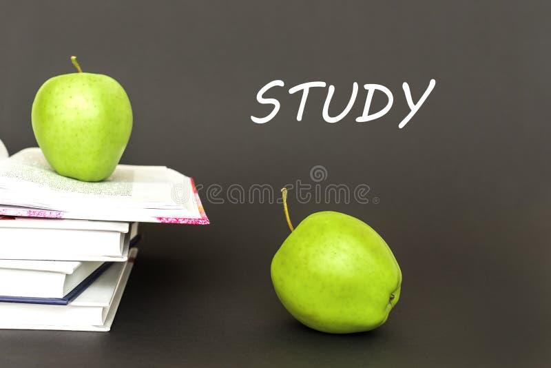 Tekststudie, twee groene appelen, open boeken met concept stock afbeeldingen