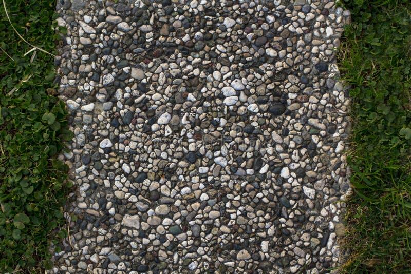 Tekstur płytki mali kamienie i zielona trawa zdjęcia stock