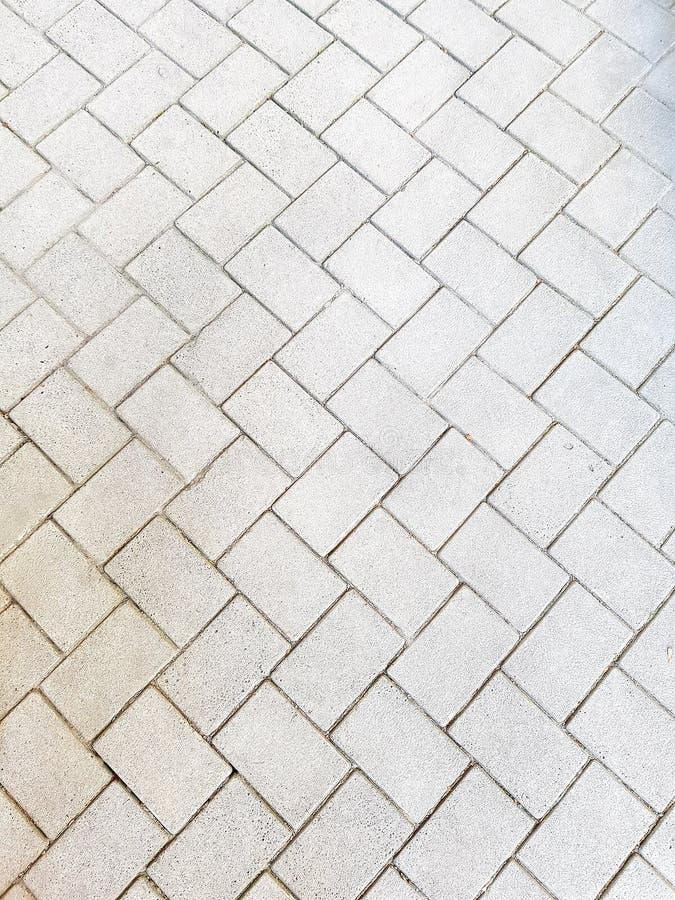 Tekstura brukowe cegiełki szare Droga od szarych starych brukowych cegiełek zdjęcie royalty free