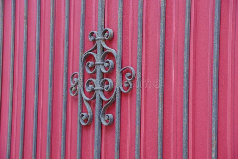 Tekstura czarni stalowi prącia i dokonany wzór na czerwonej metal ścianie obrazy stock