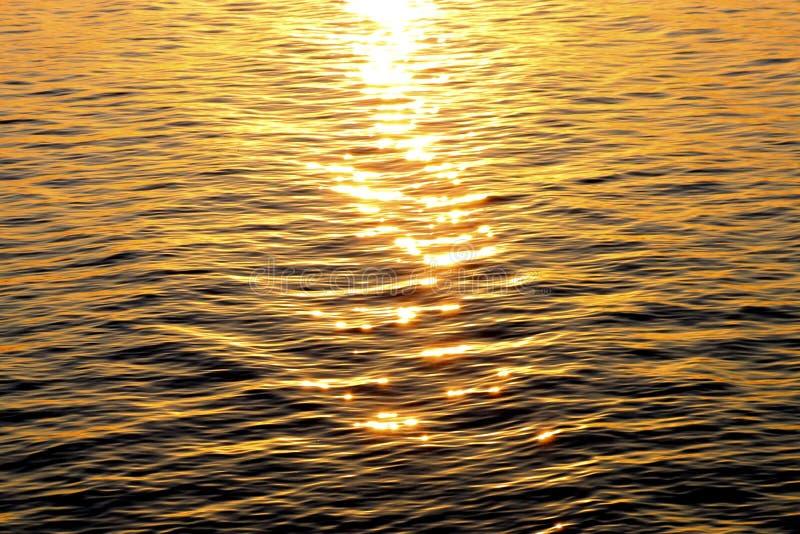 Tekstura czochry na wodzie z jaskrawymi słońce głównymi atrakcjami podczas zmierzchu obrazy stock